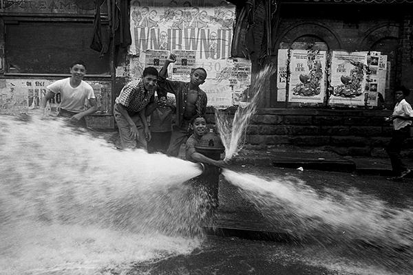 Kinder spielen in der Sommerhitze an einem Hydranten und bespritzen vorbeifahrende Autos in New York City.