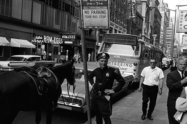 Ein Polizist steht neben seinem Pferd an einer Stra?e in Manhattan in New York City.