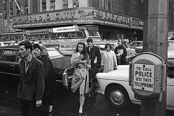 Fu?g‰nger ¸berqueren im Regen eine mit im Stau stehenden Autos gef¸llte Stra?e vor der Radio City Music Hall in New York City.