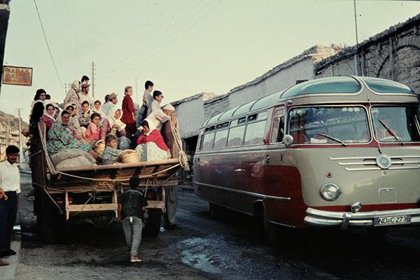 Ein mit Passanten beladener LKW neben einem modernen Reisebus auf einer Hauptstra?e nahe der syrischen Pforte.