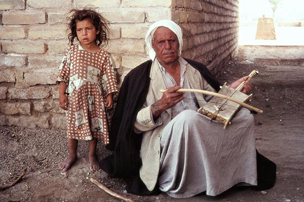 Ein M‰dchen steht neben einem blinden Mann, der an einer Stra?enecke auf einem Kamaneheh spielt.