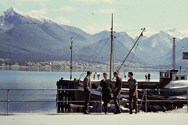 M‰nner stehen vor einem Fischerboot im Hafen von Andalsnes im Romsdalfjord.