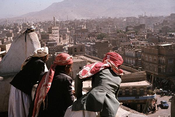 Jemeniten blicken vom Dach eines Museums auf die Stadt Sanaa.