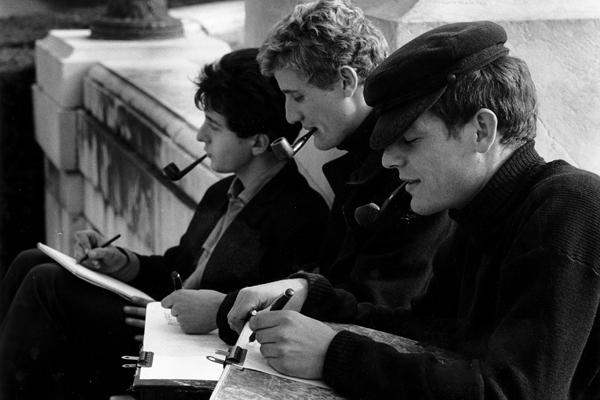 Drei Pfeife rauchende Kunststudenten fertigen im Park des Schloss Versailles Skizzen an.