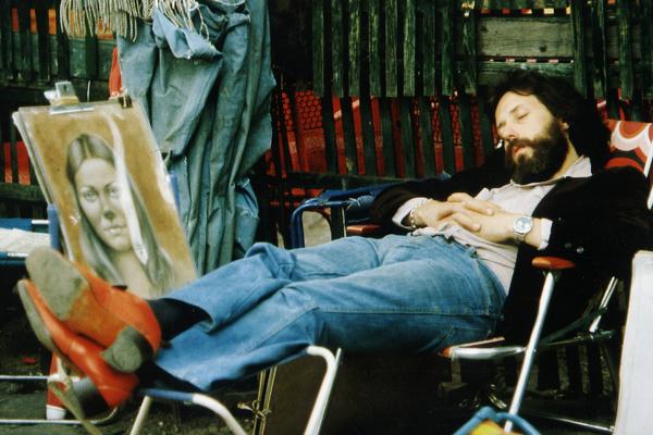 Junger Maler auf dem Montmartre schläft auf einem Stuhl, neben ihm Porträts.