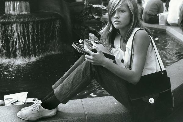 Mädchen mit Kofferradio sitzt an einem Brunnen im Universitätsviertel