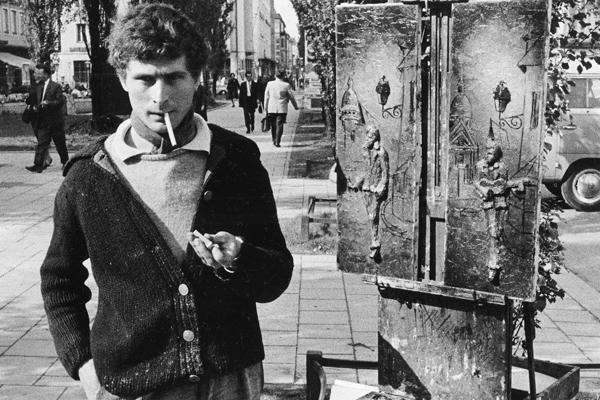 Ein junger Künstler raucht eine Zigarette neben seinem Gemälde in der Leopoldstraße in München.