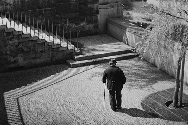 Ein älterer Herr mit Hut und Stock an der Wittelsbacher Brücke in München.