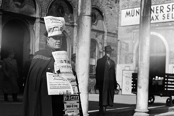 Ein Zeitungshändler bietet Zeitungen vor dem Hauptbahnhof in München zum Verkauf an.