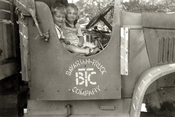 """Zwei Kinder in einem alten Lastwagen der Marke """"Bavarian Truck Company""""."""