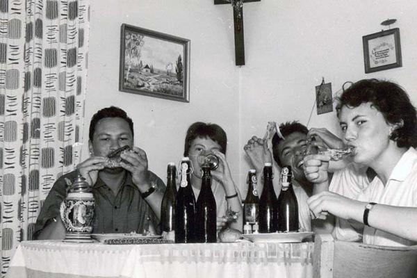 Eine Familie isst zusammen Hendl vom Wienerwald an der Amalienstraße. An der Amalienstraße wurde der erste Wienerwald gegründet mit dem Slogan:  ?Heute bleibt die Küche kalt, wir gehen in den Wienerwald?.