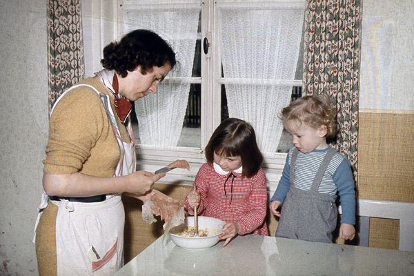 Eine Mutter bereitet mit ihren beiden Kindern in der Küche das Essen vor.