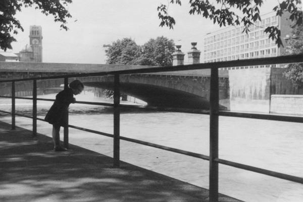Ein Mädchen steht an einem Zaun an der Isar in München. Im Hintergrund sieht man die Ludwigsbrücke, das Deutsche Museum und das Deutsche Patentamt (1. Bauabschnitt).