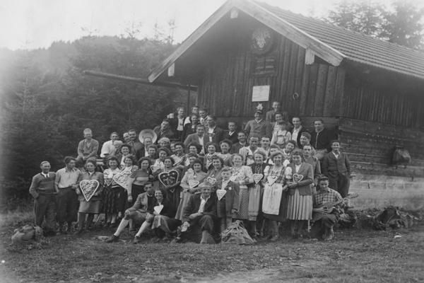 Eine Gruppe von Menschen steht vor einem Jägerhaus (undatierte Aufnahme).