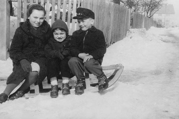 Drei Kinder auf einem Schlitten in Mistelbach (Oberfranken). Die zwei Kinder auf der rechten Seite sind Geschwister; das linke Mädchen ist die Tante der beiden. Die Tante ist nur fünf Jahre älter als das Mädchen in der Mitte.