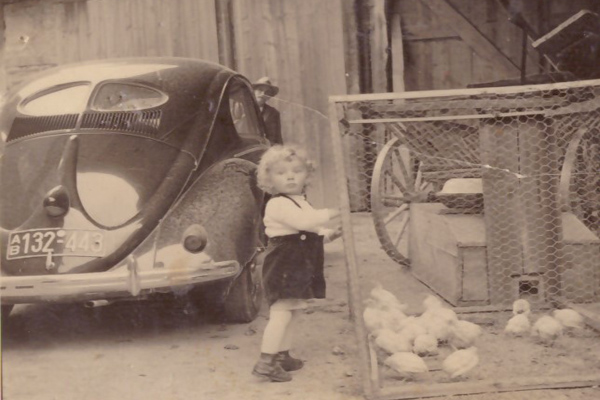 Ein kleiner Junge steht neben einem Hühnerstall auf einem Bauernhof in Remlingen/Unterfranken. Links daneben ist ein VW Käfer.