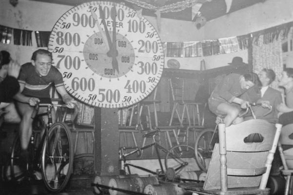 Männer veranstalten ein Hometrainer-Wettrennen auf Fahrrädern.