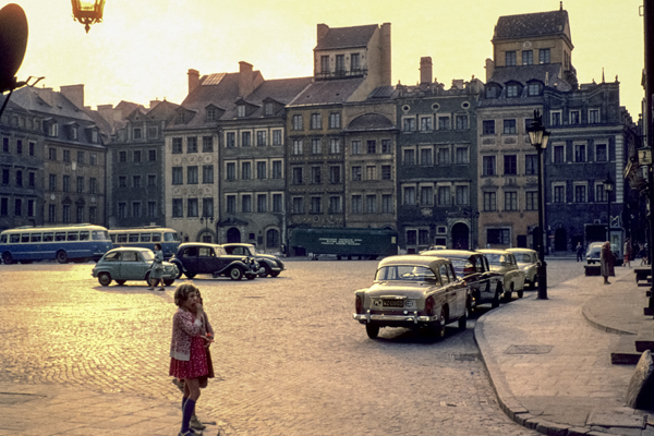 Ein junges Mädchen steht auf dem historischen Alten Markt in Warschau im Abendlicht.