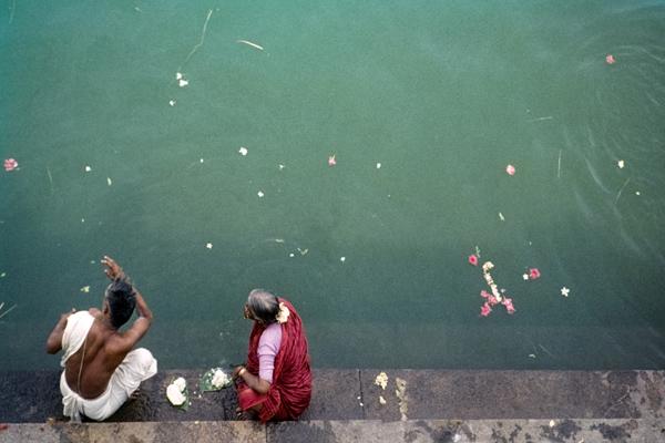 Zwei Pilger - ein älterer Mann und eine ältere Frau - sitzen am Rande des Tempelbeckens des Shivanganga-Tempelteiches des Nataraja-Tempels.