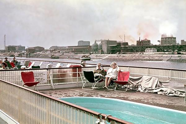 Blick vom Oberdeck eines Passagierschiffes auf dem Rhein auf sonnenbadende Gäste und Industrieanlagen.