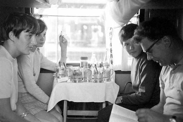 Passagiere sitzen mit Getränken an einem Tisch in einem Zug bei Brest-Litowsk.