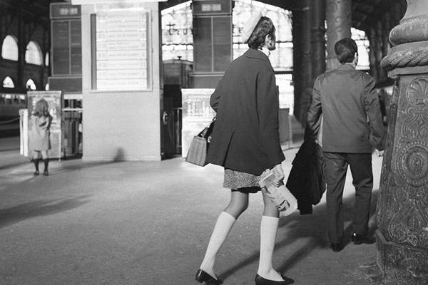Frau mit Baskenmütze, Rock, Strümpfen und Stöckelschuhen auf dem Bahnhof Paris Gare du Nord.