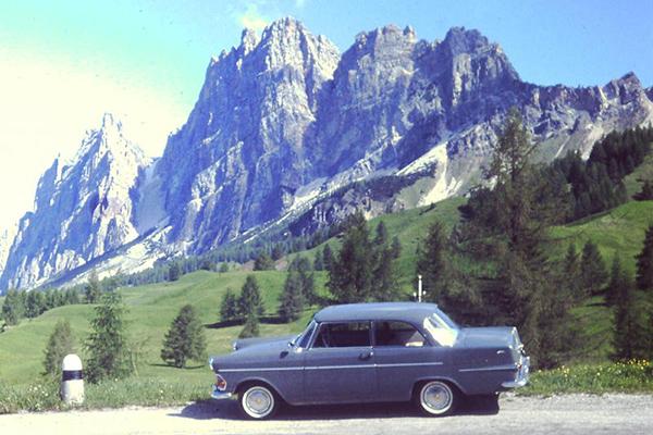 Ein Opel steht geparkt am Straßenrand vor einer Bergkulisse in den Dolomiten.