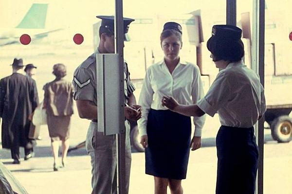 Ein Zollbeamte und zwei Flugbegleiterinnen am Eingang des Flughafen Lod.