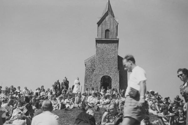 Gläubige feiern einen Gottesdienst (Bergmesse) vor der Tabor-Kapelle. Das Bild zeigt die Kapelle vor einem Brand und dem anschließenden Wiederaufbau 1970/71. Heute trägt sie den Namen Hochfellnkapelle.