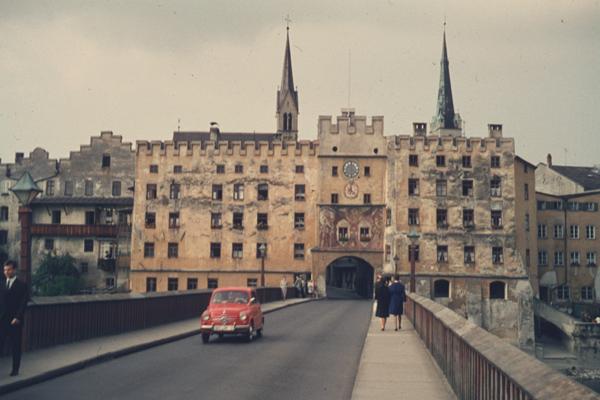 """Stadttor an der Innbrücke in der Stadt Wasserburg am Inn. Menschen spazieren die Straße entlang, ein Auto überquert die Brücke. Im Hintergrund sind die Türme der Heilig-Geist-Spitalkirche und der Kirche """"Unserer Lieben Frau"""" zu sehen."""