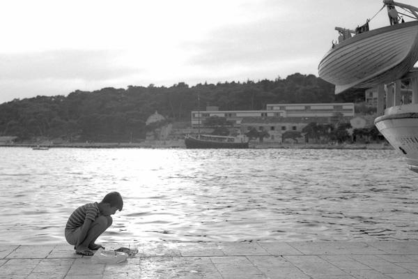 Junge spielt am Hafen von Hvar und rechts im Bild ein Rettungsboot.