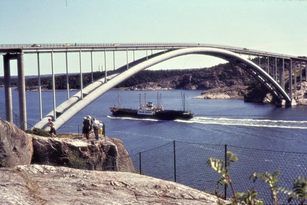 Ein Frachter unter einer modernen Rohrbogenbrücke mit einer Spannweite von 278 Metern an der Insel Tjörn.