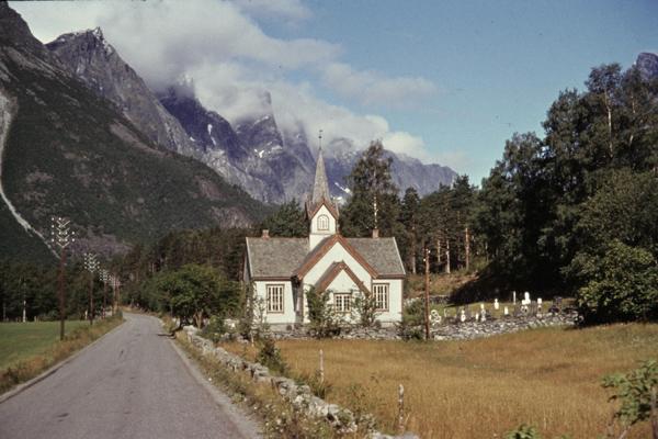 Eine Kirche im skandinavischen Baustil vor einer Bergkulisse im Romsdal-Tal.