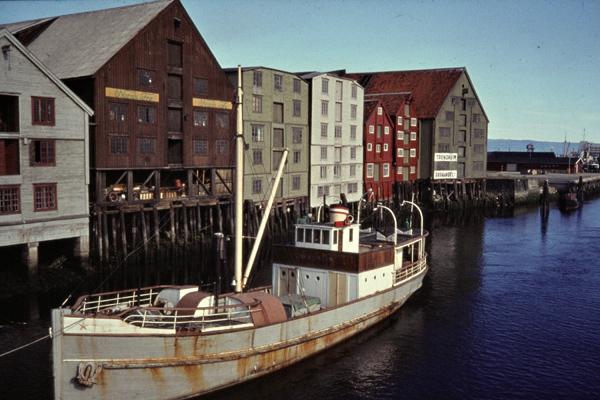 Ein Fischerboot auf dem Nidelv-Fluss vor alten Lagerhäusern im Hafen von Trondheim.