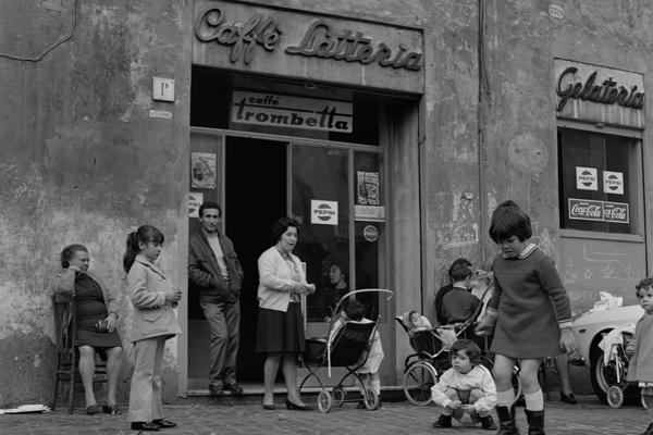 Kinder spielen auf der Straße vor einem Café in Rom.