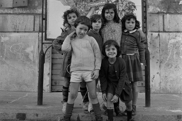 Eine Gruppe von Kindern posiert für ein Foto vor einer Reklame auf einer Straße in Rom.