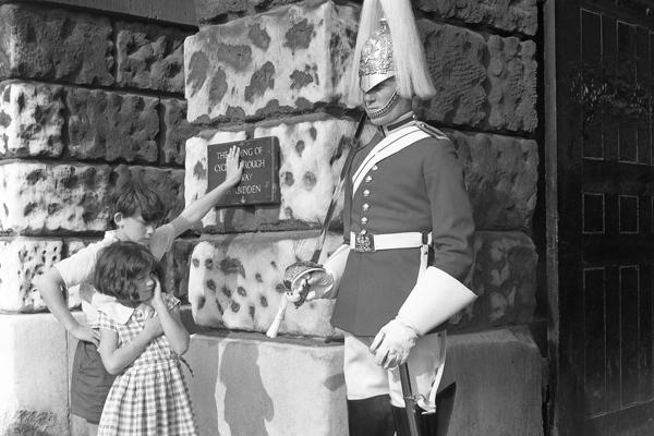 Kinder bestaunen britischen Gardisten vor dem Palace of Whitehall in London.