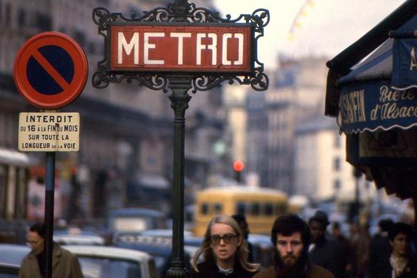 Passanten und ein Schild der Metro in Paris.