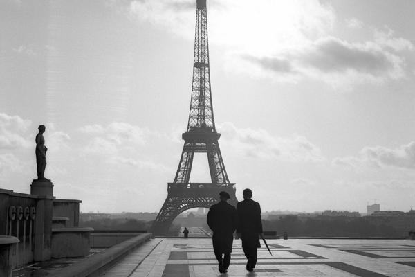 Zwei Männer, einer Mit Baskenmütze, einer mit Regenschirm, nach einem Regenschauer auf dem Marsfeld vor dem Eiffelturm in Paris.
