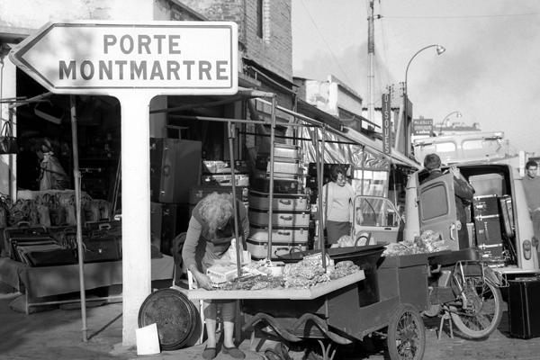 Schild (Porte Montmartre) und Verkäufer auf dem Flohmarkt (Marche aux puces) am Porte de Clignancourt in Paris.