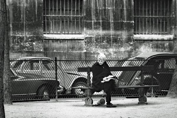 Frau auf einer Bank, dahinter ein Zaun und Autos in Paris.