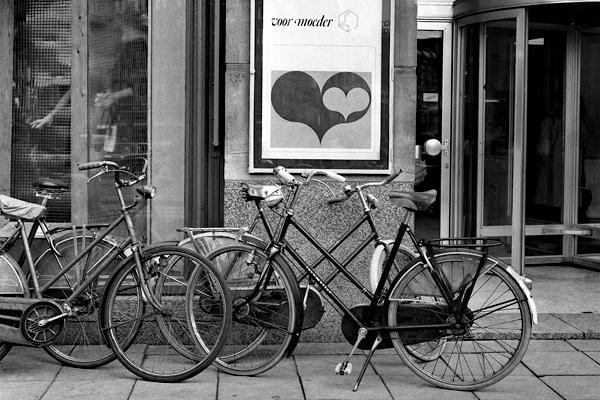 Bild (Voor moeder)  und Hollandräder vor einem Gebäude in Amsterdam.