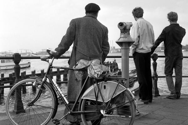 Amsterdam: Bild zeigt Männer die Schiffe am Hafen betrachten und im Vordergrund einen Mann mit Hollandrad.
