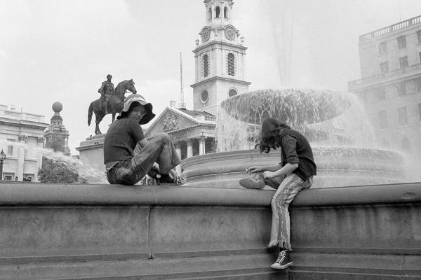 Trafalgar Square in London: Bild zeigt eine Kirche, ein Reiterdenkmal und Jugendliche auf einer Mauer vor einem Brunnen.
