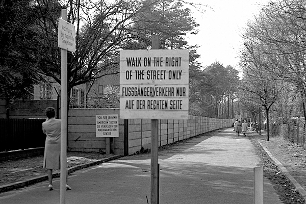 """Mauer am Weg zur Enklave Steinstücken in Berlin-Wannsee und Schilder (""""Fussgängerverkehr nur auf der rechten Seite"""", """"Achtung! Hier beginnt die Sowjetzone"""", """"Sie verlassen den amerikanischen Sektor"""")."""