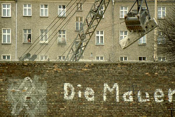 Bau der neuen Berliner Mauer aus Betonfertigteilen. Im Vordergrund die Mauer eines Hauses mit der Aufschrift 'Die Mauer' das zu Ost-Berlin gehörte und abgerissen wird. Im Hintergrund ein Wohnhaus.