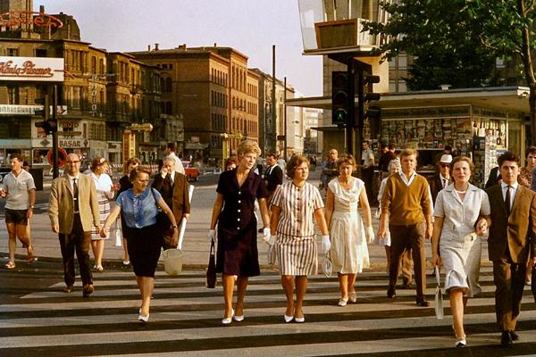 Frauen mit weißen Handschuhen und Handtasche und Männer im Anzug am Kurfürstendamm in Berlin überqueren einen Zebrastreifen und im Hintergrund ein Zeitungskiosk.