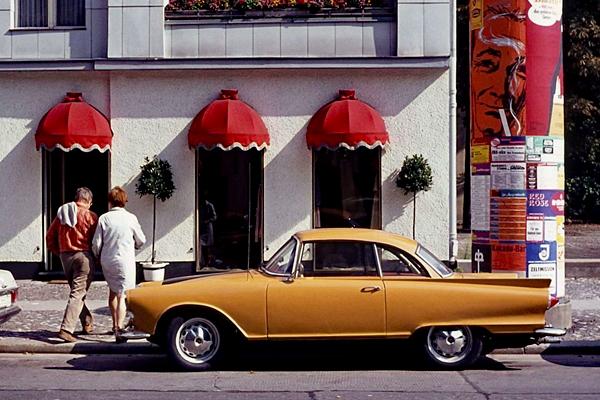 Berlin Kurfürstendamm: Bild zeigt ein Paar und Autos am Straßenrand.