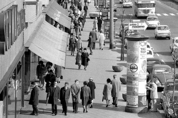 Tauentzienstraße in Berlin. Bild zeigt Passanten vor Geschäften und Straße mit Autos.