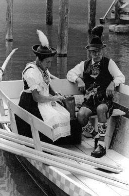 Ein älteres Ehepaar in oberbayerischer Sonntagstracht vor der Abfahrt mit einem Boot auf dem Königssee.